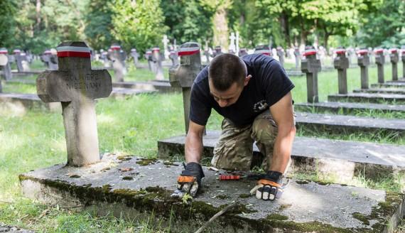 Wolontariusze sprzątają groby żołnierzy poległych w bitwie białostockiej, fot. Monika Kalicka